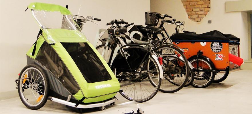 Stationnement de vélos, vélo-cargo et remorque dans un local vélo en immeuble d'habitation. @FUB
